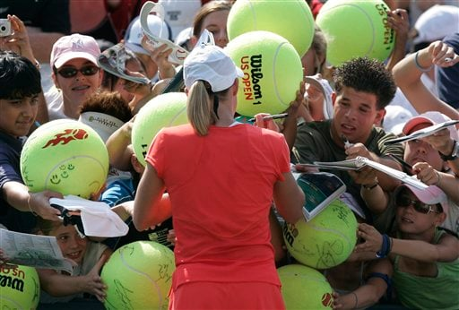 Justine Henin of Belgium signs autographs after her victory over Tsvetana Pironkova of Bulgaria at the US Open tennis tournament in New York on Wednesday.