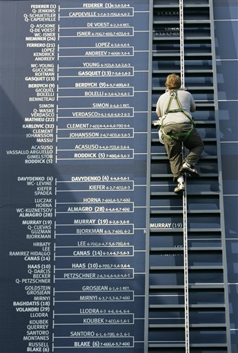 A worker climbs a ladder to add to the men's singles bracket board at the US Open tennis tournament in New York on Thursday.