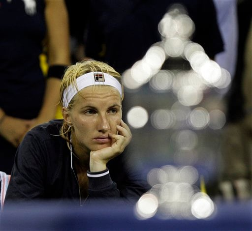 Svetlana Kuznetsova of Russia sits behind the championship trophy after being defeated by Justine Henin of Belgium in two sets in the women's finals at the US Open tennis tournament in New York on Saturday.