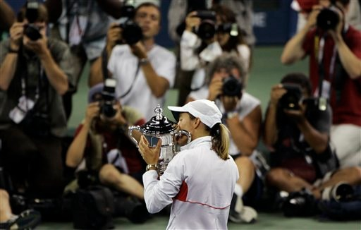 Justine Henin of Belgium kisses her championship trophy for photographers after defeating Svetlana Kuznetsova of Russia in the women's finals at the US Open tennis tournament in New York on Saturday.