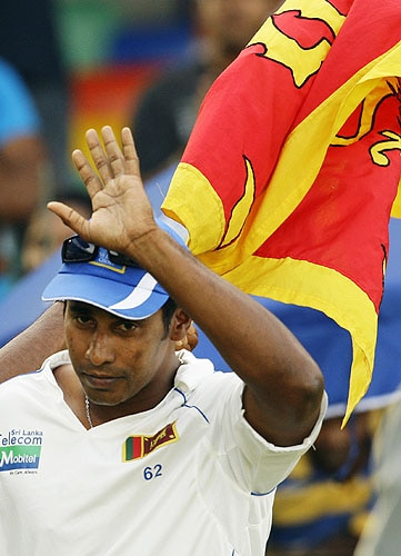 Chaminda Vaas waves to the crowd in the backdrop of Sri Lankan flag at a presentation ceremony after end of play on the last day of the third Test between Sri Lanka and Pakistan in Colombo. (AP Photo)