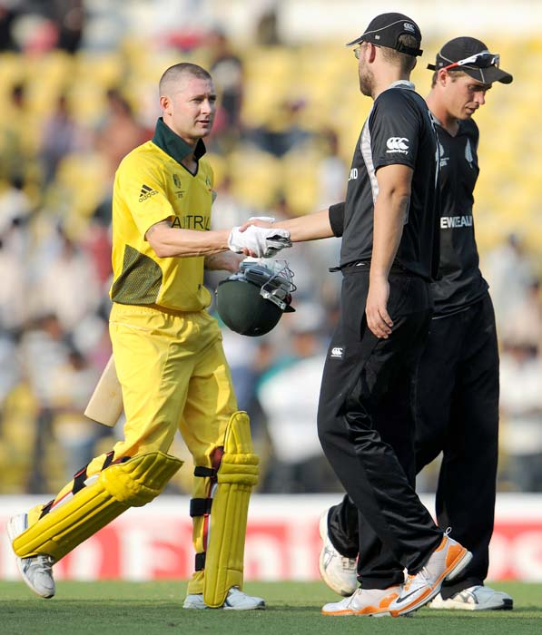 Australian batsman Michael Clarke shakes hands with New Zealand captain Daniel Vettori as Tim Southee walks off after their World Cup match at the Vidarbha Cricket Association Stadium Stadium in Nagpur. Australia won by seven wickets with 96 balls remaining. (AFP Photo)