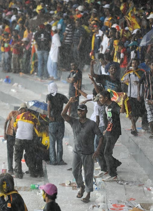 Sri Lankan fans dance in the rain as a heavy thunderstorm disrupts the World Cup match between Australia and Sri Lanka at the R. Premadasa Stadium in Colombo. (AFP Photo)