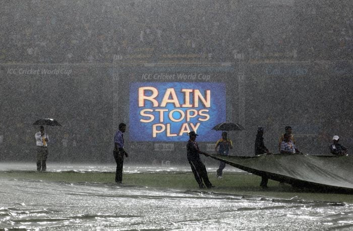 Ground staff work with the covers as rain stops play during the 2011 ICC World Cup Group A match between Australia and Sri Lanka at R. Premadasa Stadium in Colombo. (Getty Images)