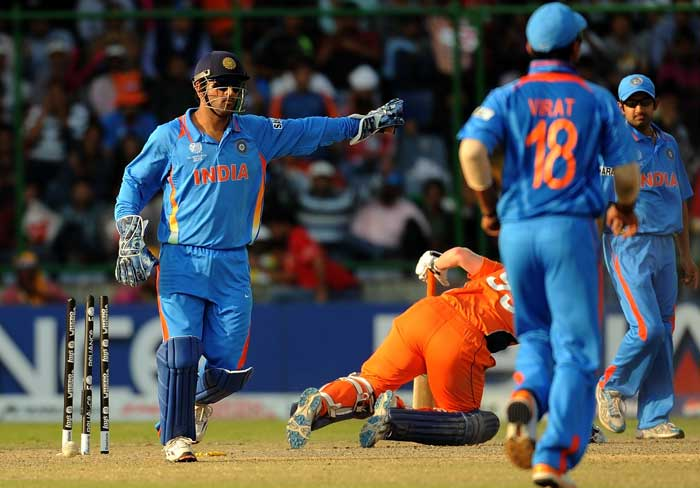 Mahendra Singh Dhoni celebrates the run out of Tom de Grooth during the ICC World Cup match between India and Netherlands at the Feroz Shah Kotla Stadium in New Delhi. (AFP Photo)