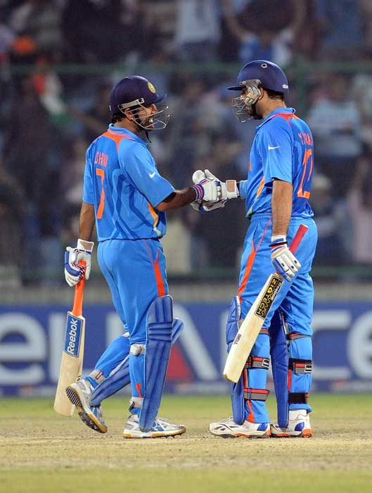 Yuvraj Singh congratulates captain Mahendra Singh Dhoni after the winning the match during the ICC World Cup match between India and the Netherlands at The Feroz Shah Kotla Stadium in New Delhi. India won by 5 wickets. (AFP Photo)