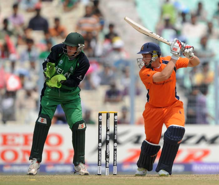 Wesley Baressi keeps his eyes on the ball after playing a shot as Niall O'Brien looks on during the Group B match between The Netherlands and Ireland in the World Cup 2011 tournament at the Eden Gardens in Kolkata. (AFP Photo)