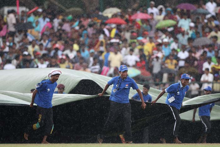 Groundstaff pull covers across the field as rain stops play during the Pakistan v Zimbabwe 2011 ICC World Cup Group A match at the Pallekele Cricket Stadium in Kandy. (Getty Images)