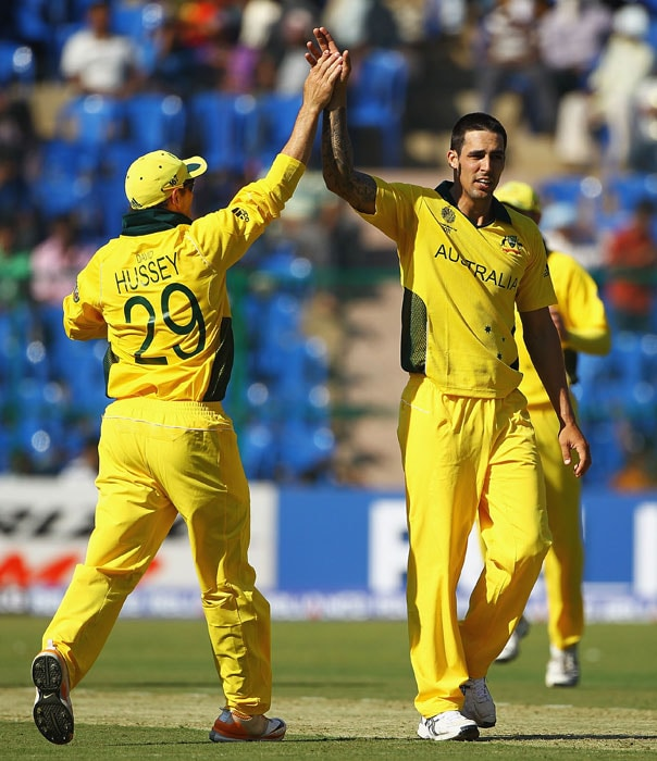 Mitchell Johnson is congratulated by David Hussey after claiming the wicket of Yuvraj Singh during the 2011 ICC World Cup warm-up game between India and Australia at the M. Chinnaswamy Stadium in Bangalore. (Getty Images)