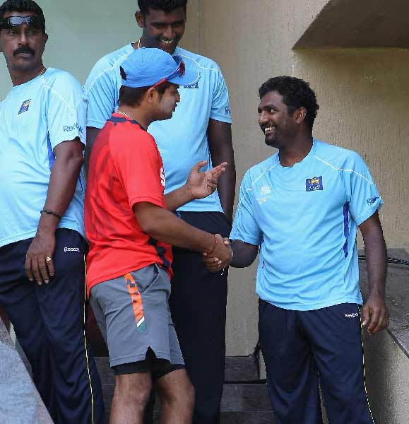 Suresh Raina shakes hands with Muttiah Muralitharan at the Wankhede Stadium.