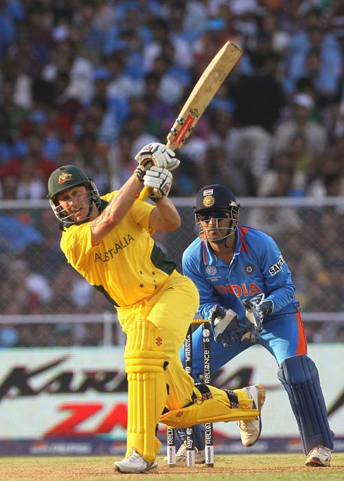 David Hussey hits a six over long on with MS Dhoni looking on during the 2011 ICC World Cup quarter final match between Australia and India at the Sardar Patel Stadium in Ahmedabad. (Getty Images)