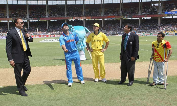 MS Dhoni tosses the coin while Ricky Ponting looks on ahead of the 2011 ICC World Cup quarter final match between Australia and India at Sardar Patel Stadium in Ahmedabad. (Getty Images)