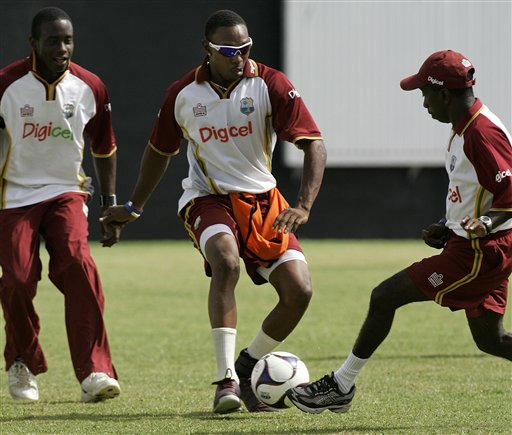 West Indies' all-rounder Dwayne Bravo, center, drives with a soccer ball guarded by assistant coach David Williams, right, and teammate Xavier Marshall, while warming up for a training session at the Antigua Recreation Ground in St. John's on Wednesday, May 28, 2008. The second cricket Test match between West Indies and Australia begins on Friday.