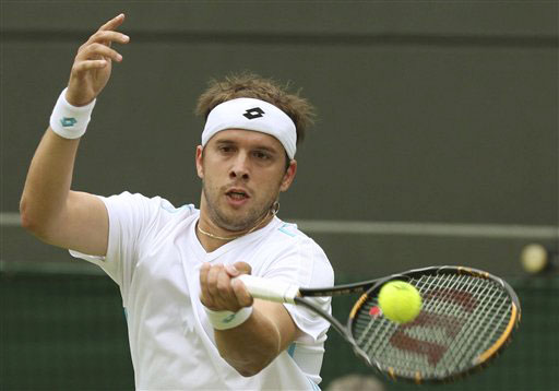Gilles Muller of Luxembourg returns to Robin Soderling of Sweden during their Gentlemen's Singles first round match at Wimbledon. (AP Photo)