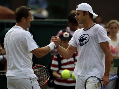 Andy Roddick shakes hands with Swedish veteran Jonas Bjoirkman, after a practice session on an outside court at Wimbledon. (AP Photo)