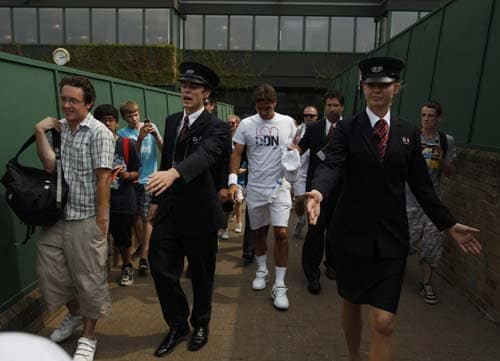 Switzerland's Roger Federer is escorted to an outside court for a practice session at Wimbledon. (AP Photo)