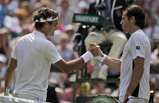 Roger Federer, left of Switzerland acknowledge greet Tommy Haas, right of Germany after their semi-final match on centre court at Wimbledon on Friday, July 3, 2009. (AP Photo)