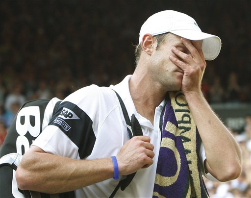 Andy Roddick of US holds his face as he leaves the court after defeating Britain's Andy Murray, in their men's singles semi-final on the Centre Court at Wimbledon on Friday, July 3, 2009. (AP Photo)