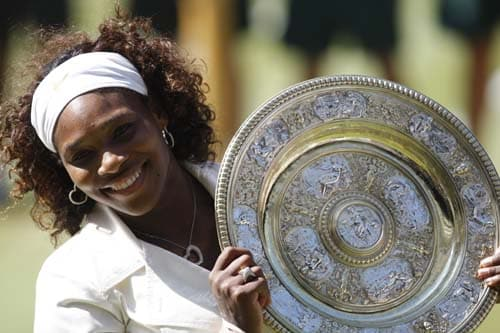 US' Serena Williams,hold the trophy, after defeating her sister Venus to win the women's singles final on the Centre Court at Wimbledon. (AP Photo)
