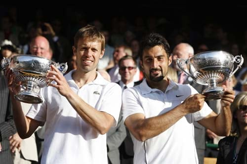 Canada's Daniel Nestor and Serbia's Nenad Zimonjic hold up their trophies, after defeating brothers Mike and Bob Bryan of the US, in the men's doubles final on the Centre Court at Wimbledon. (AP Photo)