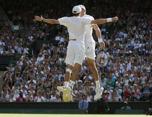 Brothers Mike, foreground, and Bob Bryan of the US, celebrate a point, during the men's doubles final against Canada's Daniel Nestor and Serbia's Nenad Zimonjic, on the Centre Court at Wimbledon. (AP Photo)