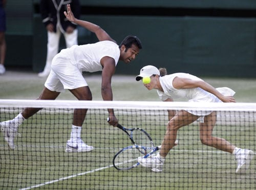 India's Leander Paes and Zimbabwe's Cara Black play a return to Germany's Anna-Lena Groenfeld and Bahamas Mark Knowles during their mixed doubles final match on the Centre Court at Wimbledon. (AP Photo)