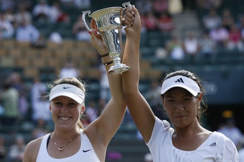 Thailand's Noppawan Lertcheewakarn and Australia's Sally Peers hold the trophy after beating France's Kristina Mladenovic and Croatia's Silvia Njiric during the girls doubles final match on Day 13 at the 2009 Wimbledon at the All England Club. (AFP Photo)