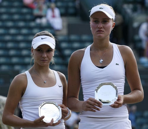 France's Kristina Mladenovic and Croatia's Silvia Njiric hold the runners up trophy after losing to Thailand's Noppawan Lertcheewakarn and Israel's Shahar Peer during the girls doubles final match on Day 13 at the 2009 Wimbledon at the All England Club. (AFP Photo)