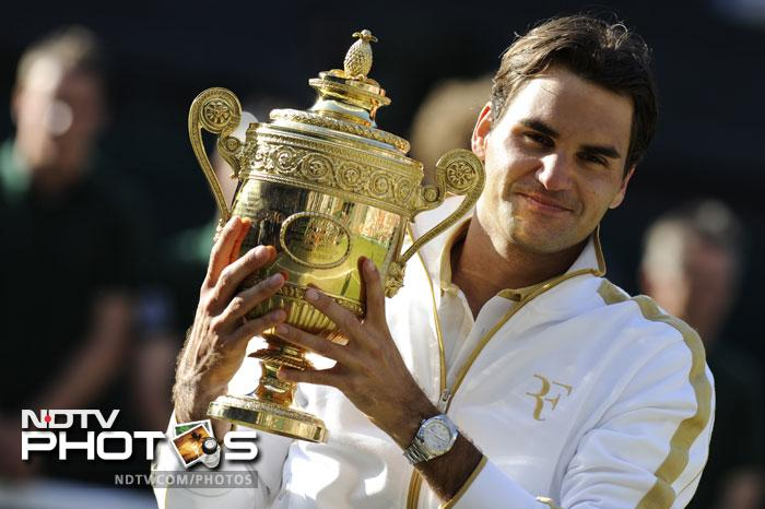 Roger Federer was knocked out by Jo Wilfred Tsonga in the quarter finals of Wimbledon 2011. 2012 was 'his year' though, with record-equalling 7th Wimbledon title after a win over fierce compatriot Andy Murray. On his 'favourite' court, he would now want to go 'one up' on Pete Sampras in 2013. (AFP Photo)