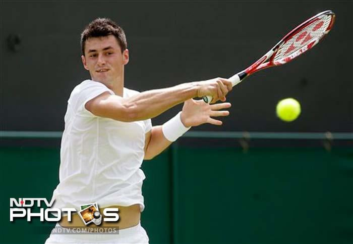Bernard Tomic overcame exhaustion and dizziness for a grueling first-round win - 7-6 (8), 7-6 (3), 3-6, 2-6, 6-3 - over 21st-seeded American Sam Querrey.