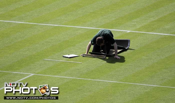 A member of the ground-staff inspects the playing surface before the start of a match on Monday.