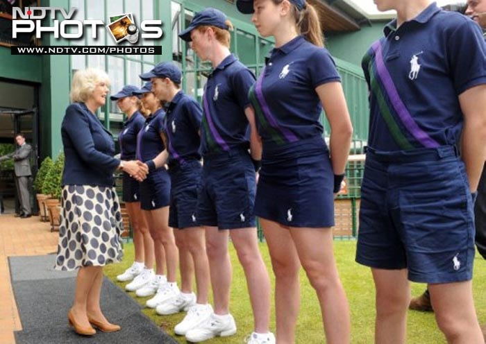 Camilla, wife of Prince Charles, and The Duchess of Cornwall (L) shakes hands with Adam Tomes as she meets ball boys and girls on the third day of the Wimbledon Tennis Championships at the All England Tennis Club, in southwest London.