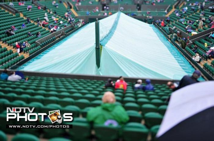 Tennis fans wait for the rain to clear on Court 2 as the start of play is delayed on the third day of the 2011 Wimbledon Tennis Championships at the All England Tennis Club, in south-west London.