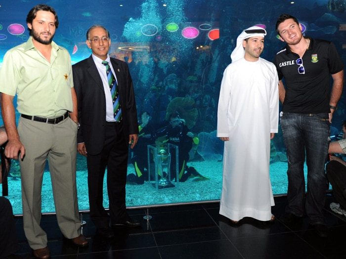 South African captain Graeme Smith, Pakistan skipper Shahid Afridi, ICC chief executive Haroon Lorgat and chief executive office Emaar Retail LLC Arif Amiri pose in front of the Dubai Mall aquarium, where South African cricketer Morne Morkel and Dale Steyn are posing underwater with the ICC World Cup trophy. (AFP PHOTO)