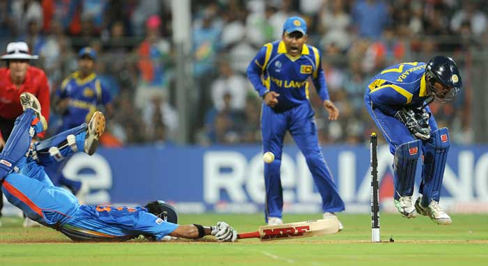 Indian batsman Gautum Gambhir slides into his crease as Sri Lankan wicketkeeper Kumar Sangakkara attempts to gather the ball. (AFP Photo)