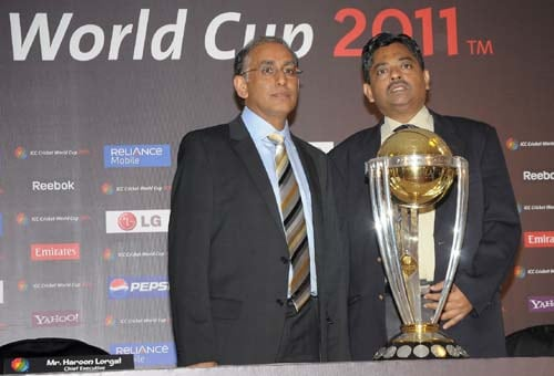 In this handout photograph from the International Cricket Council (ICC), Haroon Lorgat, Chief Executive Officer of the ICC and Profressor Ratnakar Shetty, Tournament Director pose with the ICC Cricket World Cup 2011 trophy during the unveiling ceremony in Mumbai. (AFP Photo)
