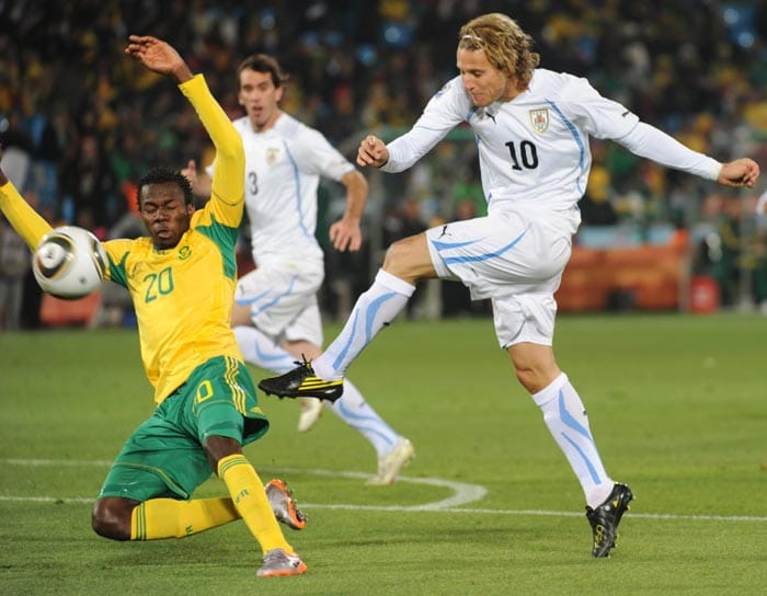 """Having drawn their first game against France, Uruguay knew that a win over the hosts would put them in contention for a place in the next round. And star striker Diego Forlan delivered on the promise by shooting from 25 yards out to give the Uruguayans the lead.<br><br> Never afraid to shoot when within sight of goal, Forlan let fly a scorcher which looped over the South African keeper Khune with the help of a slight but crucial deflection off home captain Aaron Mokoena, the ball clipped the crossbar en route to going in. <br><br><a href=""""http://ndtv.footballindia.com/2010_worldcup/fan_survey.aspx"""" class=""""fg fn fl fs12"""">Pick your best goal</a>"""