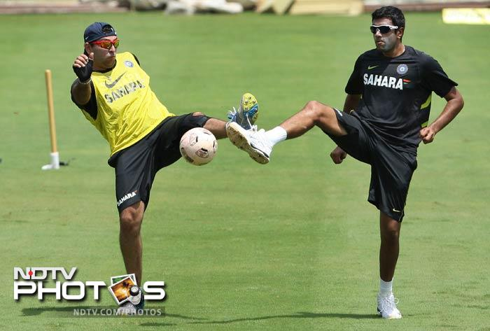 Yuvraj and Ashwin (right) stretch as they try and gain control of the football.