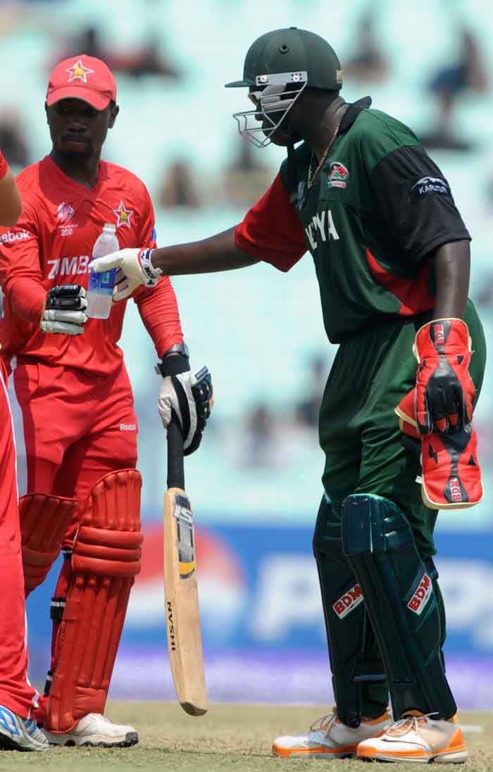 Kenya wicketkeeper David Obuya shares a drink of water with Zimbabwe batsman Tatenda Taibu during their Group A match. (AFP Photo)