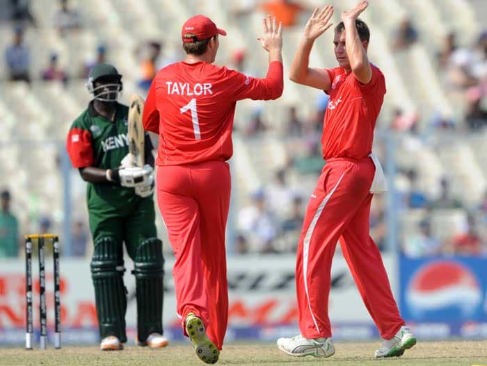 Zimbabwe cricketer Brendan Taylor greets teammate Ray Price after the dismissal of Kenya player Steve Tikolo. (AFP Photo)