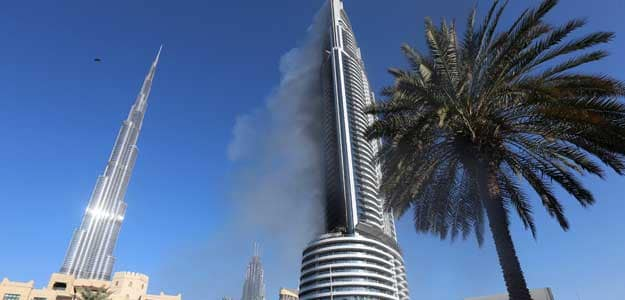 Plumes of smoke rise from the 63-storey Address Downtown Dubai hotel and residential block near the Burj Khalifa, the tallest building in the world, a day after the hotel caught fire on New Year's Eve, in Dubai, January 1, 2016.