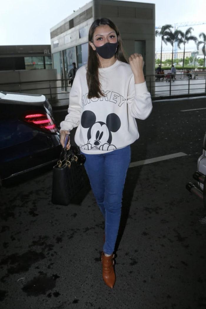 Hansika Motwani kept her airport look casual in a Mickey Mouse print sweatshirt.