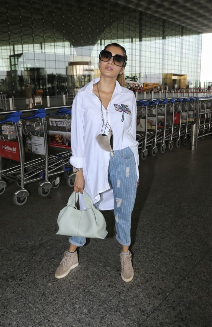 TV actress Tina Dutta kept her airport look casual yet stylish in a white shirt and blue denims.