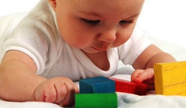 The baby starts displaying an interest in toys and games and enjoying games and dropping things.