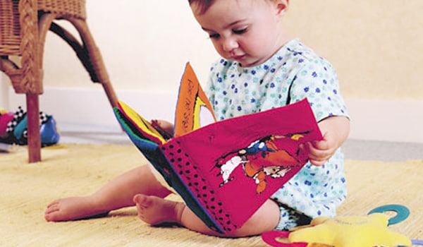 At this stage, children start learning a few simple words and try to look at some books.