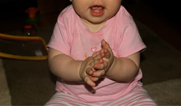 The baby will be able to clap her hands and wave goodbye. She will also show that she understands a few words and very short, simple statements.