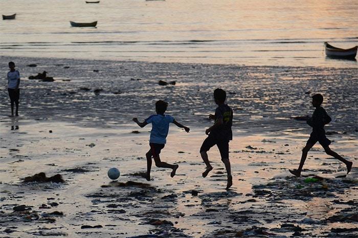 Children play football at a beach in Mumbai.
