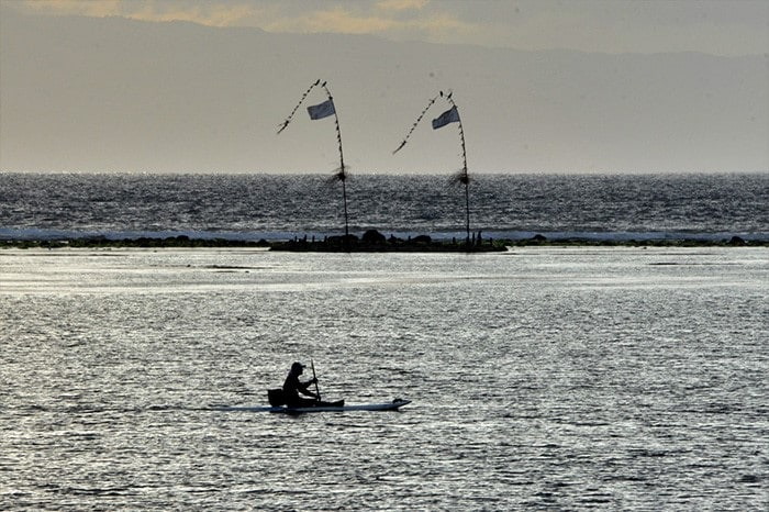 A man paddles a canoe during sunrise at a beach in Sanur on Indonesia\'s resort island of Bali.