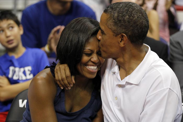 Obamas pose for Kiss Cam during a basketball match