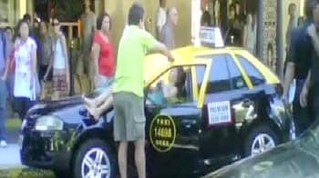 Video : Woman jumps from roof, hits taxi and survives